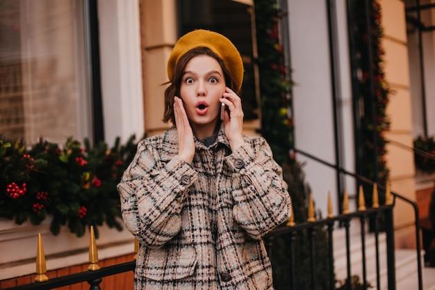 Close-up portret van vrouw praten over telefoon met geschokt gelaatsuitdrukking