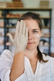 Close-up portret van vrouwelijke ambachtelijke keramist met handen gekleurd met grijze klei