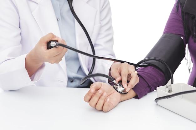 Close-up portret van vrouwelijke arts bloeddruk van een patiënt controleren