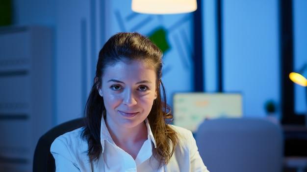 Close-up portret van zakenvrouw die lacht naar de camera na het lezen van e-mails op een laptop die 's avonds laat aan het bureau zit in een startend bedrijf. gerichte werknemer die technologienetwerk draadloos gebruikt om overuren te maken