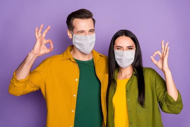 Close-up portret van zijn hij haar ze mooi aantrekkelijk gezond paar dragen veiligheidsmasker gezondheidszorg verzekering omarmen weergegeven: ok-teken knipogende geïsoleerde violet paarse kleur achtergrond