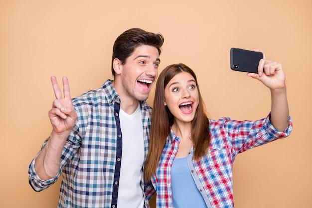 Close-up portret van zijn hij haar ze mooie aantrekkelijke mooie funky vrolijke vrolijke paar dragen geruit overhemd nemen selfie tonen v-teken geïsoleerd op beige pastel kleur achtergrond