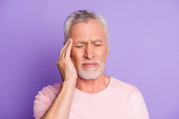 Close-up portret van zijn mooie aantrekkelijke onwel depressief uitgeput moe grijsharige man aanraken tempel slecht geïsoleerd over heldere levendige glans levendige lila paars violet kleur achtergrond