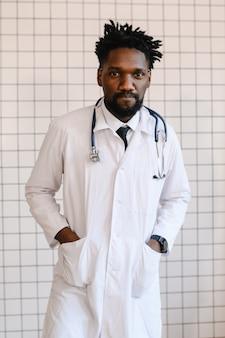 Close-up portret van zwarte arts glimlachen en kijken naar de camera.