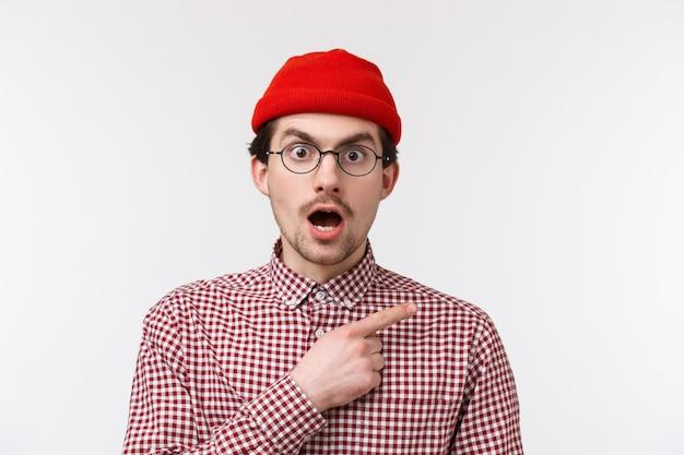 Close-up portret verrast en geschokt jonge blanke man met snor, bril en rode muts dragen, kaak laten vallen en staren alsof hij schokkend nieuws hoort, wijzend rechtsboven