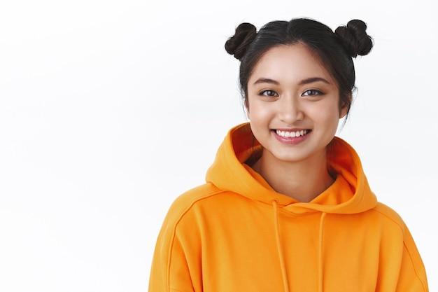 Close-up portret vriendelijk gelukkig kawaii aziatisch meisje in oranje hoodie met twee schattige haarbroodjes, gelukkig lachend, positieve vrolijke emoties tonen, staande witte muur, concept van schoonheid