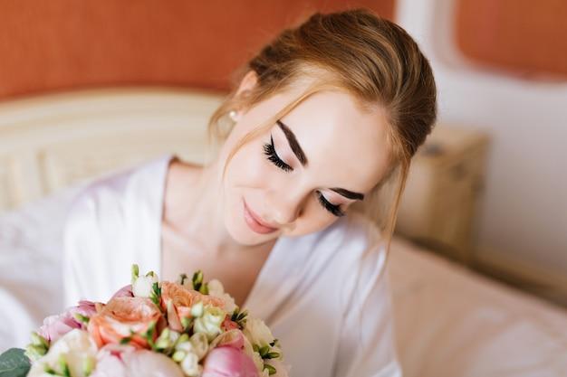 Close-up portret vrij gelukkige bruid in witte badjas in de ochtend in appartement. ze kijkt naar boeket bloemen in handen en lacht