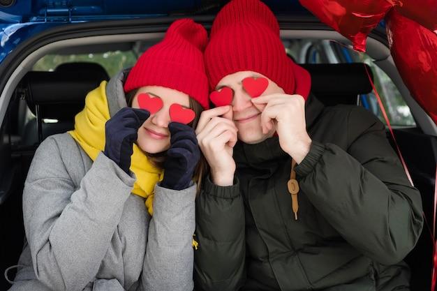 Close-up portret vrolijke paar gezichten kijken door rode papieren harten. valentijnsdag