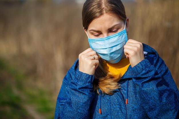 Close-up portret vrouw buiten in chirurgisch masker met rubberen oorbandjes. typisch 3-laags chirurgisch masker om de mond en neus te bedekken. proceduremasker van bacteriën. beschermingsconcept.