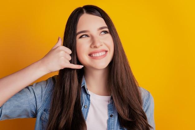 Close-up portret vrouw glimlachend vingers toon bel me terug teken kijk lege ruimte geïsoleerde gele muur achtergrond