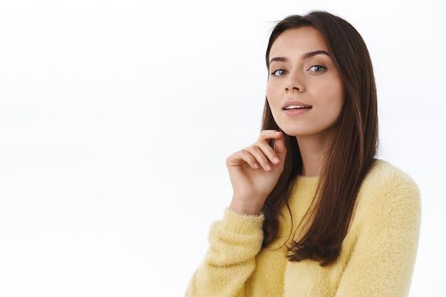 Close-up portret vrouwelijke knappe jonge zelfverzekerde vrouw met perfecte huid, geen vlekken, natuurlijke uitstraling, starende camera nieuwsgierig en brutaal, witte muur
