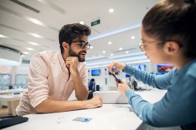 Close-up portret weergave van nieuwsgierig opgewonden gelukkig lachend jonge student bebaarde man kijken naar mobiel terwijl vrouwelijke verkoper instructie geeft voor sim plaats aan de telefoon na het kopen met bankkaart in op