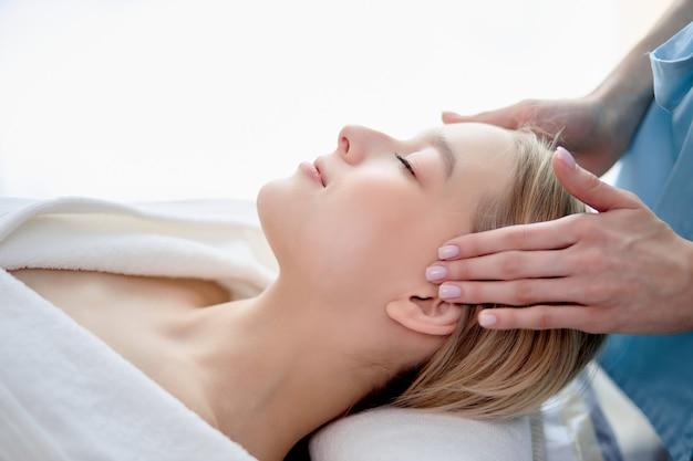 Close-up portret zijaanzicht van blonde rustige vrouw die rust heeft, ontspannen in de spa salon