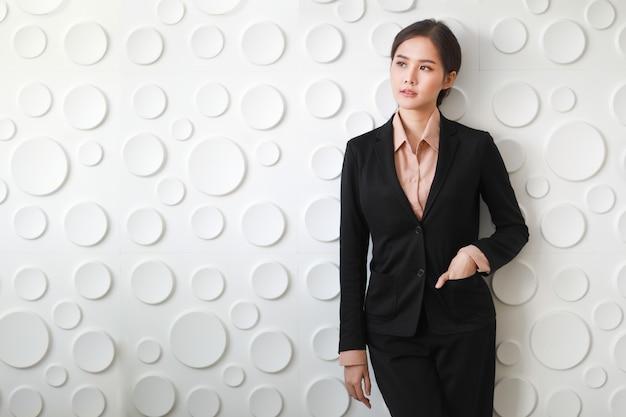 Close-up portretfoto van aziatische zakenvrouw die staat, glimlacht en hand in de tas van het pak steekt die laat zien hoe comfortabel het is om gefotografeerd te worden op een achtergrond met veel wit cirkelvormig oppervlak.