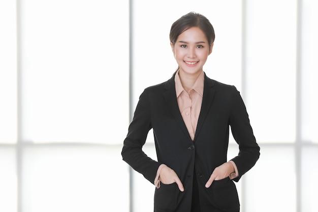 Close-up portretfoto van aziatische zakenvrouw die staat, glimlacht en hand in de tas van het pak steekt die laat zien hoe comfortabel het is om op kantoor gefotografeerd te worden.