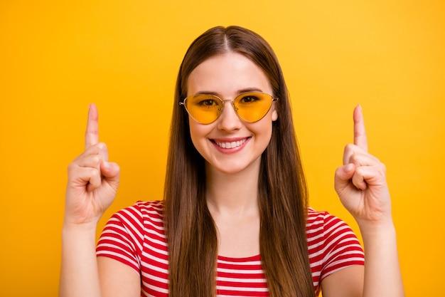 Close-up portretfoto van schattige mooie jonge promotor meisje glimlachend wijzende vingers lege ruimte suggereren opzoeken slijtage zon specs gestreept wit rood shirt levendige gele kleur achtergrond