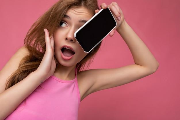 Close-up portretfoto van sexy verraste mooie positieve jonge blonde vrouw die roze topje draagt
