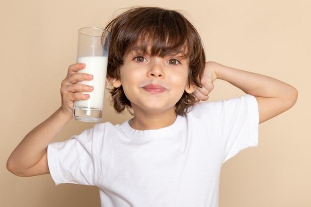 Close-up, portretweergave lachende schattige jongen schattig witte volle melk drinken op roze muur