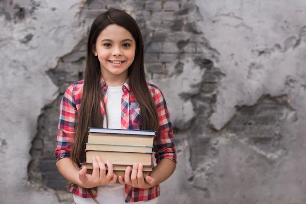 Close-up positief jong meisje dat een stapel boeken houdt