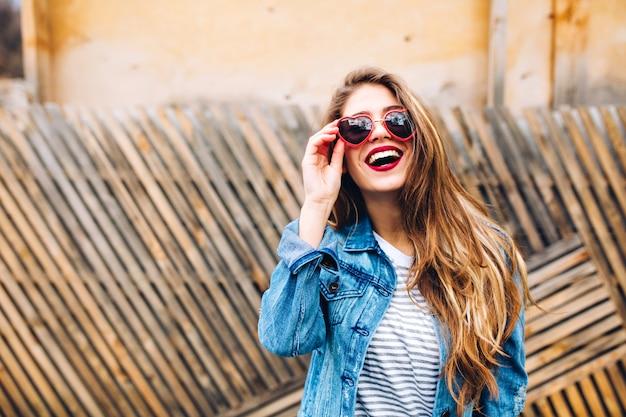 Close-up posrtait van prachtig vrouwelijk model in retro spijkerjasje, zonnebril vasthoudend en opzoeken. sensuele jonge vrouw met mooi lang haar poseren graag voor het ongewone houten hek.