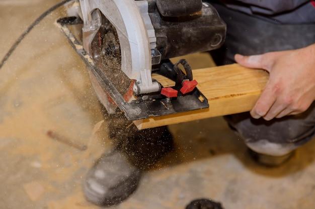 Close-up proces snijden van hand cirkelzaag op houten balk bezuinigingen op de renovatie van een huis.