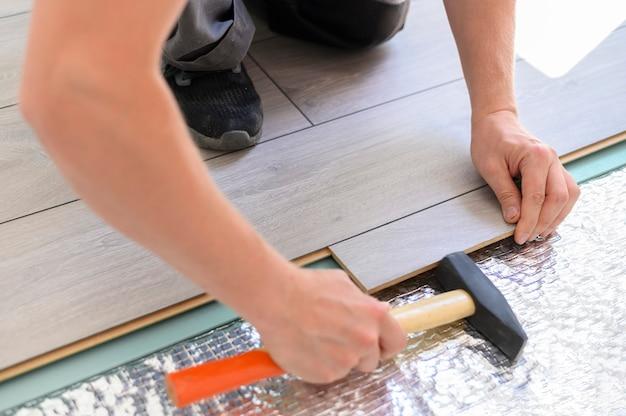 Close-up proces van het leggen van laminaat man met hamer het installeren van nieuwe gelamineerde houten vloer bovenaanzicht