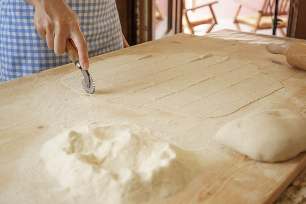 Close-up proces van zelfgemaakte vegan farfalle pasta. de kok gebruikt de rolsnijder om het deeg te snijden