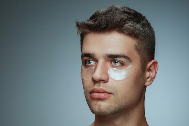 Close-up profiel portret van een jonge man geïsoleerd op grijze studio