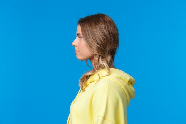 Close-up profiel portret van ernstig ogende aantrekkelijke jonge blanke vrouw met kort blond haar, op zoek naar links, staande in gele hoodie, rechtop