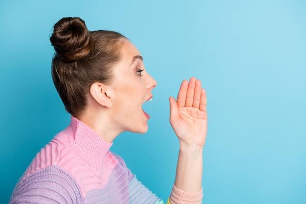 Close-up profielfoto van aantrekkelijke dame houd open arm in de buurt van mond schreeuwen nieuwigheid informatie menigte mensen open mond dragen warme gestreepte trui geïsoleerde blauwe kleur achtergrond