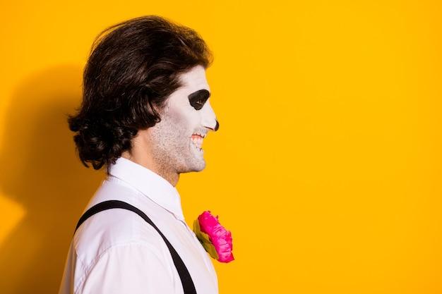 Close-up profielfoto van griezelige schepsel kerel kijken lege ruimte stralende toothy lachende bang kinderen dragen wit overhemd roos dood kostuum bretels geïsoleerde gele kleur achtergrond