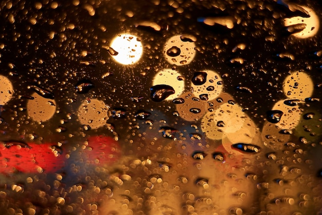 Close-up regendruppels op het oppervlak van de voorruit van de auto, met wazige stedelijke straatverlichting 's nachts