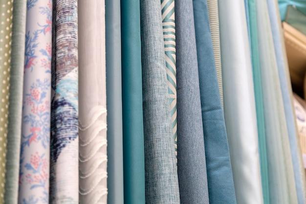 Close-up rijen stukjes stof gemaakt van katoen, polyester, tapijt en andere materialen van verschillende kleuren en prints voor het naaien van gordijnen, beddengoed en kleding