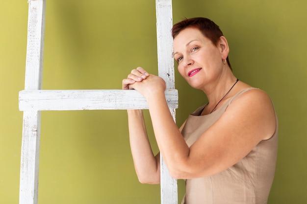 Close-up rijpe vrouw met handen op ladder