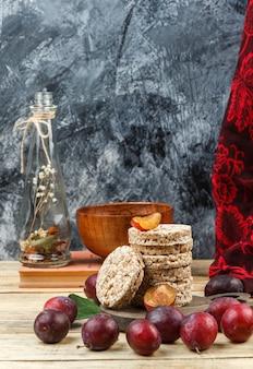 Close-up rijstwafeltjes op ronde snijplank met kruikvaas, een kom, pruimen en rode sjaal op houten bord en donkergrijs marmeren oppervlak. verticale vrije ruimte voor uw tekst