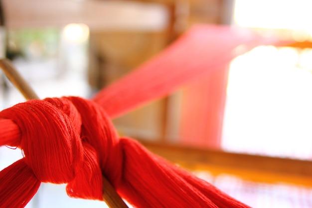 Close-up rode garens op houten weefgetouw weven klaar om te produceren.