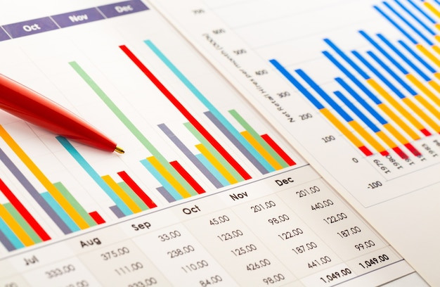 Close-up rode pen op zakelijke grafieken en diagrammen op tafel.