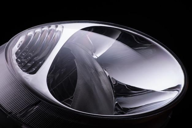 Close-up ronde autokoplampen op een zwarte geïsoleerde achtergrond