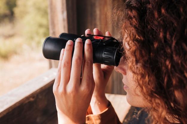 Close-up roodharige vrouw kijkt door een verrekijker