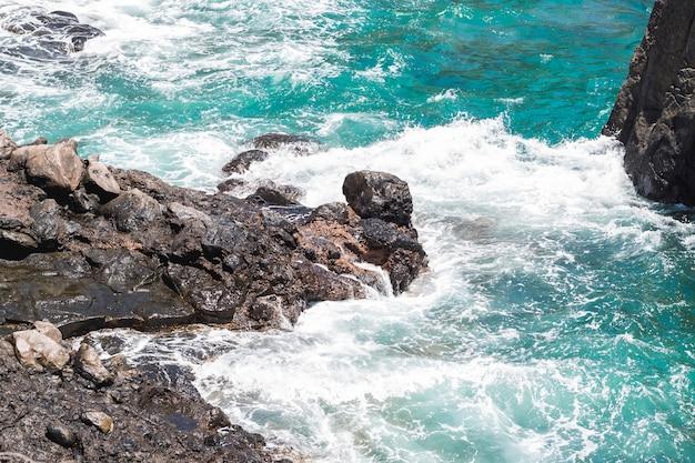 Close-up rotsachtige kust met kristallijn water