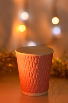 Close-up roze kop op een kerstachtergrond met een gloeiende slinger in warme kleuren. ondiepe scherptediepte.
