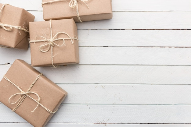 Close-up rustieke bruine papieren kerstpakket vastgebonden met touwtjes. witte houten achtergrond.