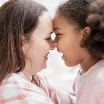 Close-up schattig jong meisje graag bij haar moeder