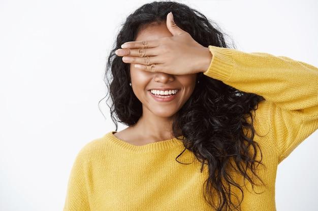 Close-up schattige vrouwelijke vrouw met krullend haar in gele trui bedek ogen met palm en lacht vrolijk, wachtend op verjaardagsverrassing, verstoppertje spelen, iets verwachten