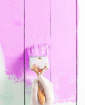 Close-up schilder man hand schilderij roze kleur op houten plank tafel met kopie ruimte, helder creatief design interieur en hoe houten oppervlak te schilderen.