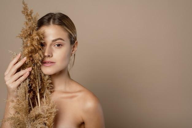 Close-up schoonheid portret van een aantrekkelijke jonge topless vrouw met bruin haar geïsoleerd op beige achtergrond, met gedroogd kruid. huid zorg concept.