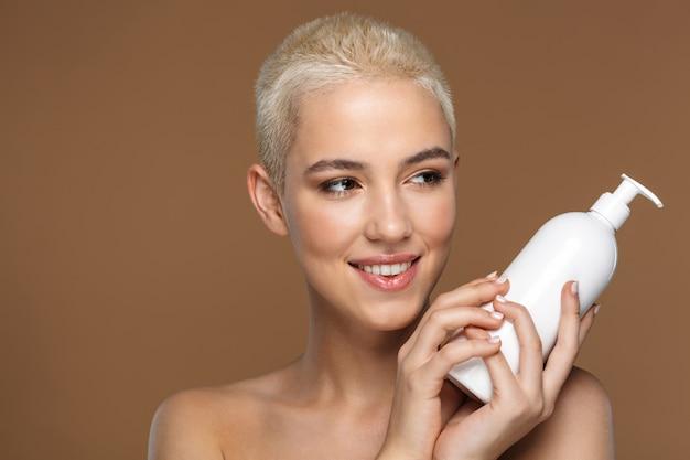 Close-up schoonheid portret van een aantrekkelijke lachende jonge blonde vrouw met kort haar poseren geïsoleerd op bruin, lege plastic container tonen