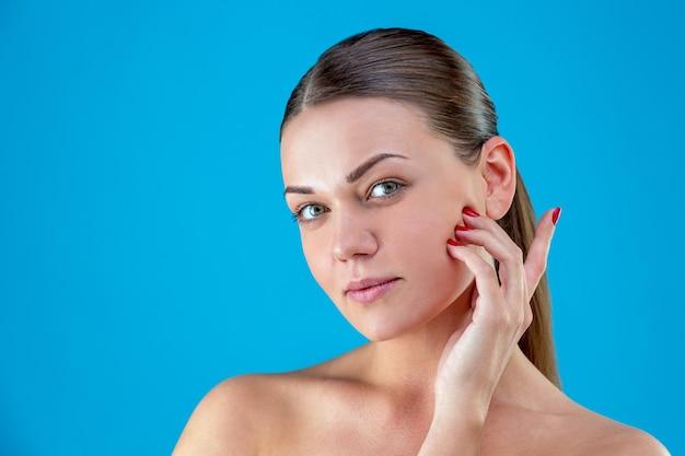 Close-up schoonheid portret van jonge vrouw brunette glimlachend en haar gezicht op blauwe achtergrond aan te raken