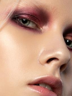 Close-up schoonheid portret van jonge vrouw met koraal rode smokey eyes. perfecte huid- en modemake-up. sensualiteit, passie, trendy make-up voor jongeren.