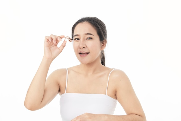 Close-up schoonheids aziatische vrouw met perfecte naakte samenstelling. opzij kijken, wimpers zwaaien met een speciaal instrument. schoonheidssalon. hoofd en schouders, profiel, studio, binnenshuis